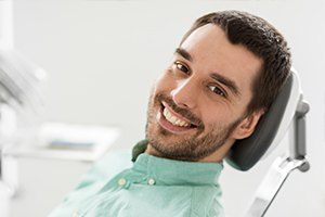 Smiling young man in dental chair