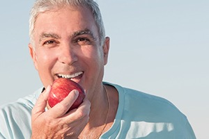 Older man eating a red apple