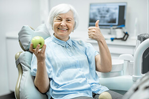 Woman with dental implants in Gorham holding apple giving thumbs up