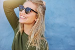 Smiling woman enjoys her dental crowns in Gorham in the sun