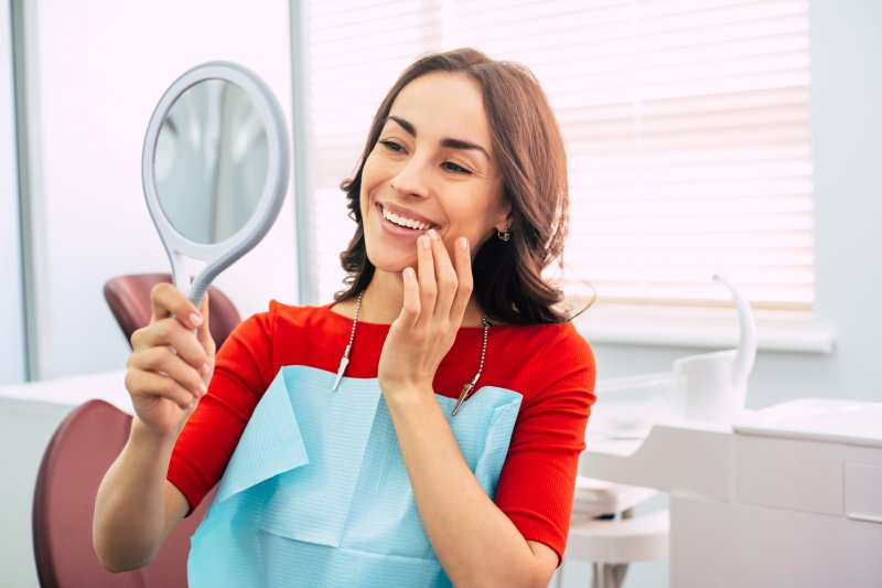 Woman smiling at reflection with dental implants