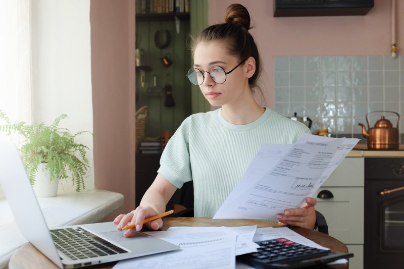 Woman reviewing dental insurance paperwork at home