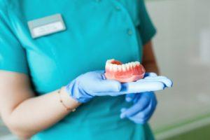 dentist holding replacement dentures in Gorham
