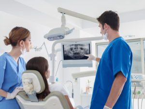 dentist showing a patient how computer-guided dental implant placement works